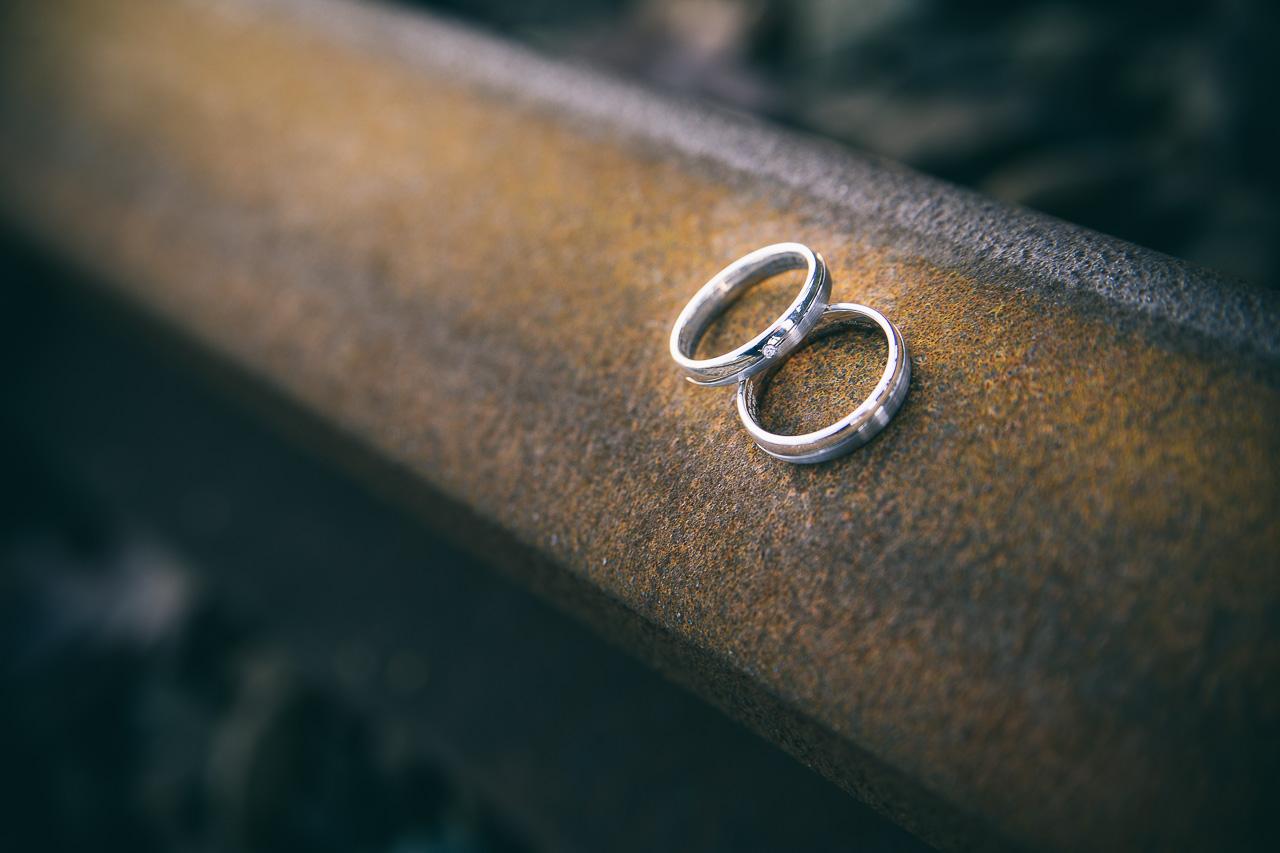 Detail fotografie trouwringen op trein rails